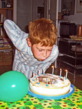 Boy blowing out his birthday candles. Nine years old boy blowing out his birthday candles Royalty Free Stock Image