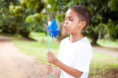 Boy blowing on pinwheel Stock Image