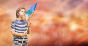 Boy blowing pinwheel over bokeh Stock Photos