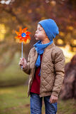Boy blowing pinwheel at park Stock Image