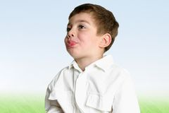 Boy blowing raspberry. Landscape view of a young boy blowing a raspberry in profile Royalty Free Stock Photography