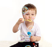 Boy blowing soap bubble. Isolated on white Royalty Free Stock Photography