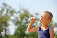 Boy blowing soap bubbles Royalty Free Stock Images