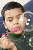 Boy blowing soap bubbles. Royalty Free Stock Image