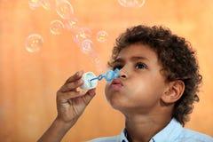 Boy blowing soap bubbles stock images