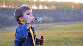 Boy blowing a soap bubbles stock footage