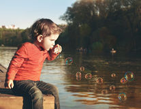 Boy blowing soap bubbles Royalty Free Stock Photos