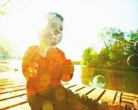 Boy blowing soap bubbles Stock Photos