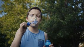 Boy blowing soap bubbles outdoors summer. Boy blowing soap bubbles outdoors summer stock video footage