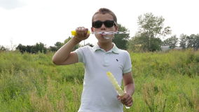 Boy blowing soap bubbles stock footage