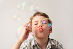 Boy blowing soap bubbles on white Royalty Free Stock Photos