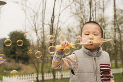 Boy blowing soapbubbles Stock Images