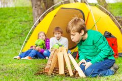 Boy blowing to burn the bonfire near yellow tent Royalty Free Stock Image
