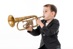 Boy blowing into a trumpet against white background Royalty Free Stock Images
