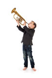 Boy blowing into a trumpet against white background Royalty Free Stock Photos
