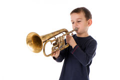 Boy blowing into a trumpet Stock Image