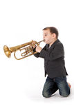 Boy blowing into a trumpet Royalty Free Stock Photos