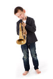 Boy blowing into a trumpet Royalty Free Stock Photography