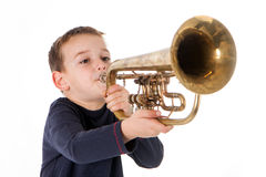 Boy blowing into a trumpet Royalty Free Stock Image