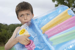 Boy Blowing Up Air Mattress Royalty Free Stock Image