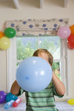Boy blowing up birthday balloons Royalty Free Stock Photography