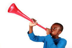 Boy Blowing Vuvuzela. Boy Blowing a red Vuvuzela royalty free stock image