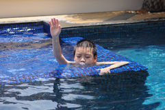A boy blowing water. At swimming pool and raise his hand stock photo
