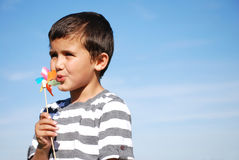 Boy blowing windmill Royalty Free Stock Photo