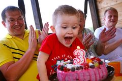 Free Boy Blows Out Birthday Cake Candles At Family Party Stock Photos - 168069673