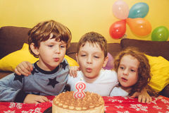 Boy blows out the candles on a birthday cake and hugs his brothe. R and sister royalty free stock image