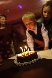 Boy blows out the candles Royalty Free Stock Photos