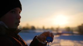 Boy blows soap bubbles in the Park with delight at winter sunset stock footage