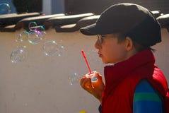 Boy blows soap bubbles. A boy plays blowing soap bubbles Royalty Free Stock Images