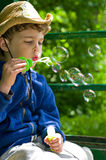 Boy blows soap bubbles. Three year old boy in the cowboy hat blows soap bubbles. On the hat the image of the Ukrainian Trident Stock Photography