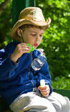 Boy blows soap bubbles. Three year old boy in the cowboy hat blows soap bubbles. On the hat the image of the Ukrainian Trident Stock Photos