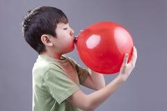 Boy blows up balloon. Stock Photos