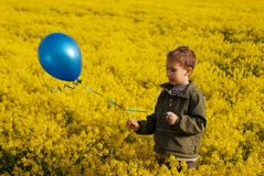 Boy with a blue balloon on a yellow field Stock Images