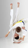 Boy with a blue belt throws boy with yellow belt Stock Photo