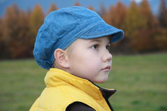 Boy with blue cap. What he is thinking about ..... ? What does he see Stock Photo