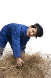 Boy in blue coverall harvesting straw Stock Photography
