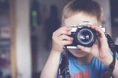 Boy in Blue Crew Neck T Shirt Taking Photo Using Minolta Dslr Camera during Daytime Royalty Free Stock Photography