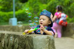 Boy in Blue Fitted Cap Playing Bubbles and Leaning on Grey Concrete Wall at Daytime Stock Images