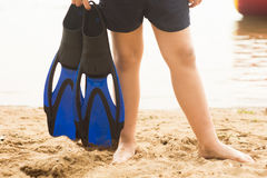 Boy in blue flippers. On sand Stock Photography
