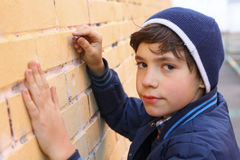 Boy in blue hat drawing on the wall Royalty Free Stock Photography