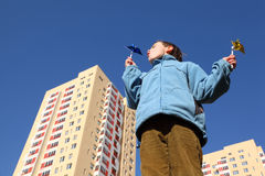 Boy in blue jacket blowing on pinwheels Royalty Free Stock Photography