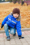 Boy in blue jacket, crouched down Stock Photography