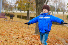 Boy in blue jacket holding the balance in his arms Royalty Free Stock Images