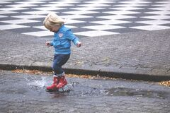 Boy in Blue Jacket Hopping on Water Puddle Stock Photography