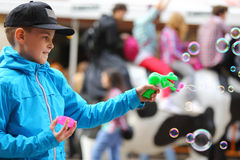 Boy in blue jacket playing with soap bubbles gun Stock Photo