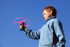 Boy in blue jacket plays with propeller Royalty Free Stock Photo